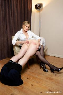 mistress-scarlet-in-black-stockings-and-heels-spanking-slave-over-the-knee