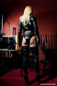 mistress-scarlet-thigh-high-boots-showing-ass-in-dungeon