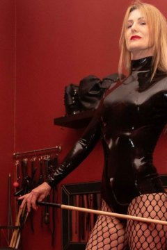 mistress-scarlet-in-fishnets-standing-in-dungeon-with-cane