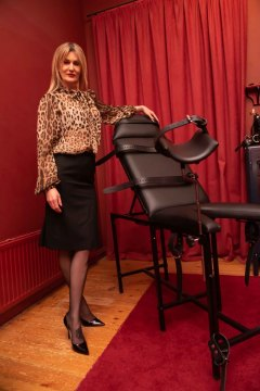 mistress-scarlet-standing-in-dungeon-wearing-stockings-heels-black-skirt-and-leopard-print